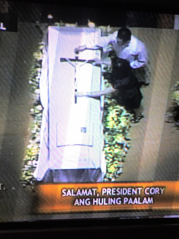 Kris Aquino, assisted by a religious, laying down a silver crucifix on top of her mom's coffin (ABS-CBN).