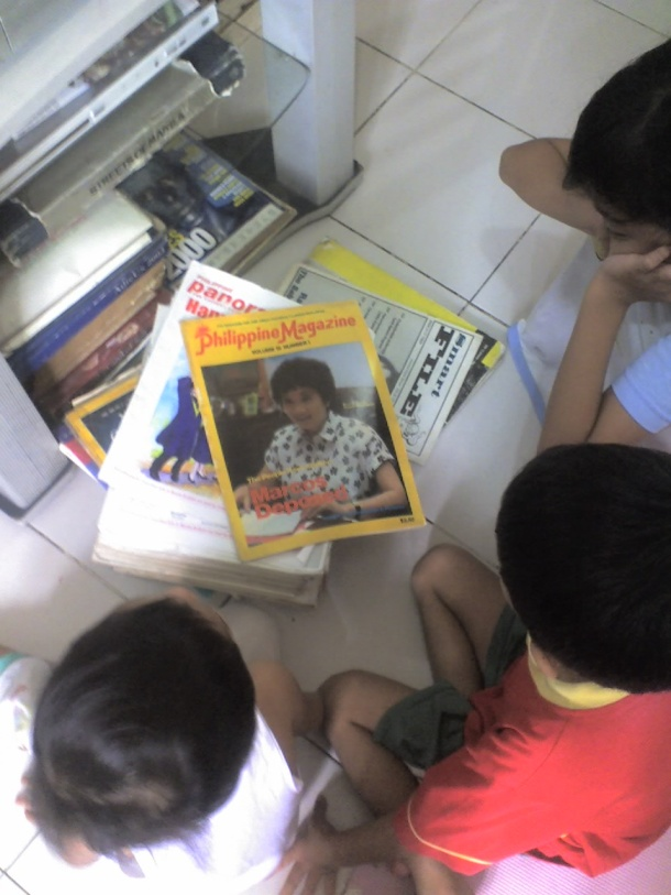 My kids watching Tita Cory's funeral on live TV (with a magazine about her, published right after the 1986 People Power Revolution)