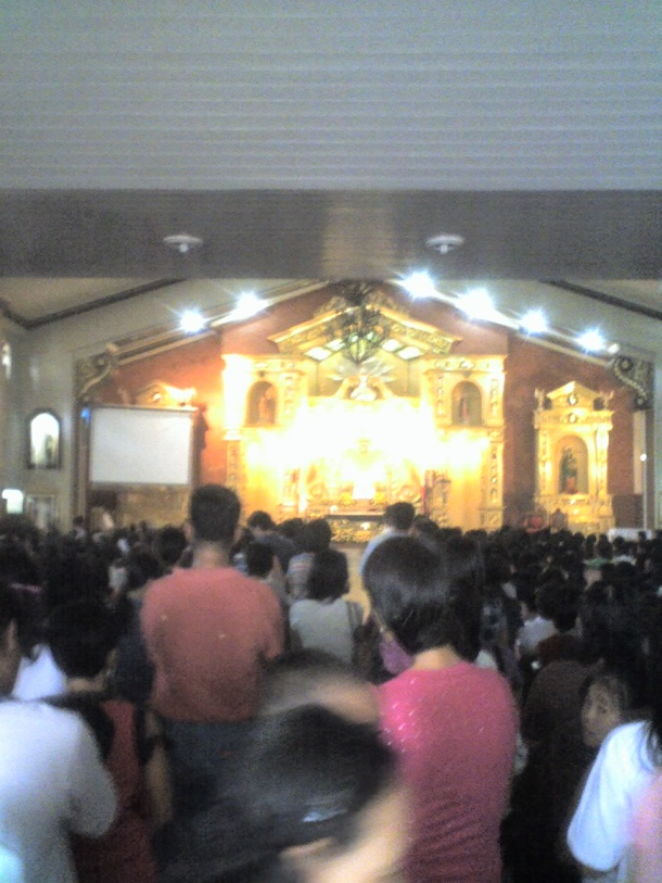 Inside the church. In front is the altar wrapped in golden lights.