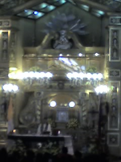 On top of the altar is the glass-covered encasement (camarín) which holds the miraculous image of Lolo Uweng. On the other side of this, a long queue of devotees patiently wait to hold the image.