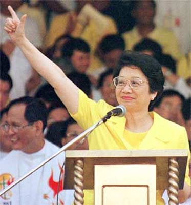 "The icon of Philippine democracy shown here in her famous yellow dress with her ""laban"" hand sign."