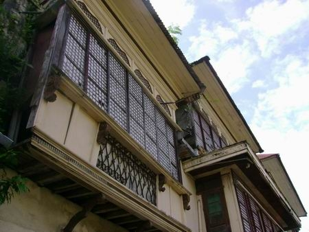 Philippine baroque: adobe ground floor; wooden second floor projecting over the sidewalk -- classic bahay-na-bató design!